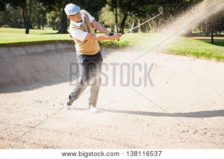Side view of sportsman playing golf on a sandbox