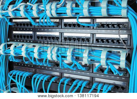 Close up of blue network internet cables connected to router patch panel in data center