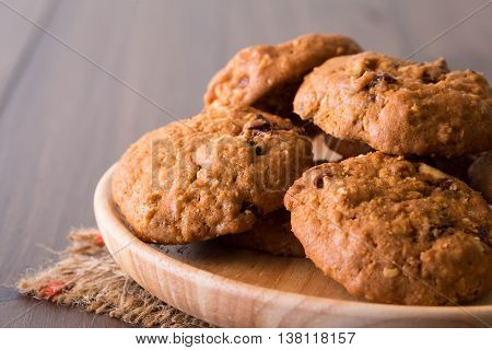 Chocolate raisin cookies arranged on a plate made of wood.