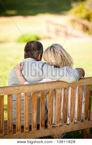 Elderly Couple Sitting On The Bench With Their Back To The Camera