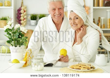 happy Senior couple  in a bathrobes  with tea reading magazine