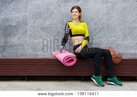 Sporty caucasian girl resting on bench with mat and gym bag after exercise
