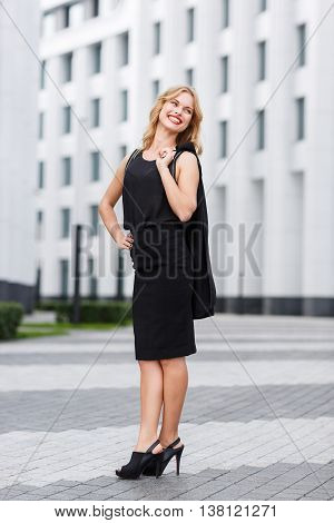 Happy young curly-headed blond woman smiling on background of new white city buildings