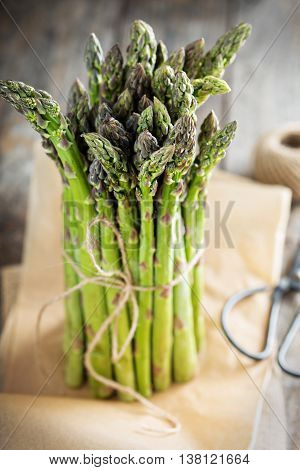 A bunch of fresh green asparagus on wooden table