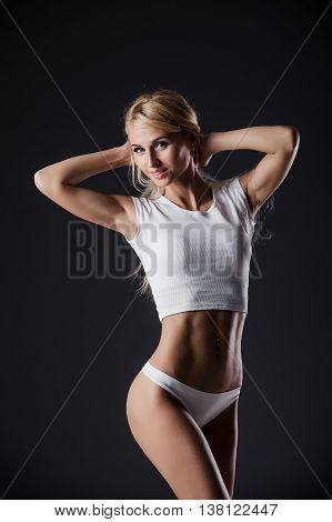 Fitness blonde woman shows her body. Fitness motivation. Perfect female sports figure. Fitness woman posing in the studio. Fitness photo shoot in the studio. Fitness bikini.