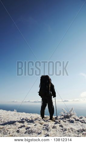 Backpacker overview winter landscape in the Crimean mountain