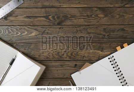Notebooks, ruler and pen on a wooden desktop