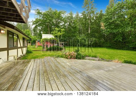 View Of Wooden Walkout Deck With Patio Area.