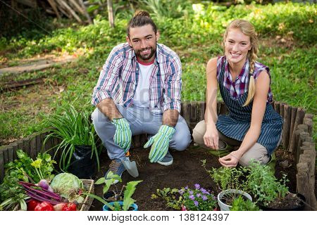 Portrait of happy young gardeners crouching with potted plants at garden