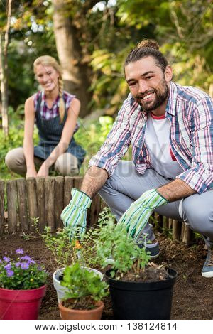 Portrait of happy young gardeners planting at botanical garden