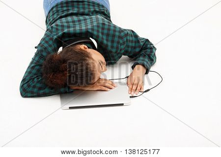 Portrait of young beautiful african girl with laptop sleeping on floor over white background. Copy space.