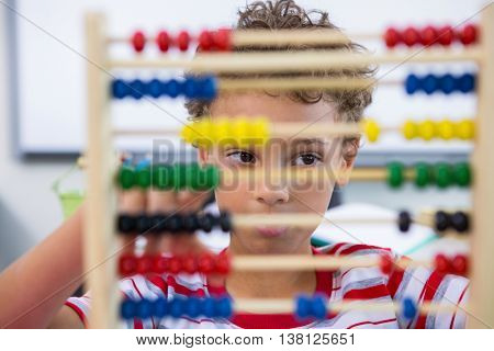 Close-up of boy playing with abacus in classroom