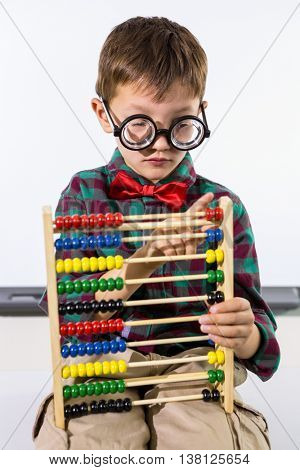 Close-up of cute boy playing with abacus against whiteboard in classroom