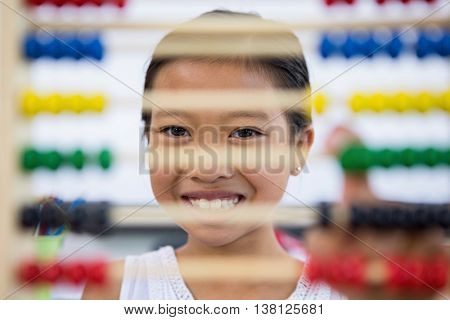Portrait of smiling girl in front of abacus in classroom