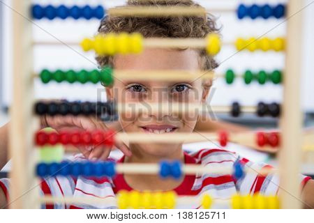 Cute boy playing with abacus in classroom at sschool