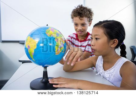 Cute elementary boy and girl looking at globe in classroom