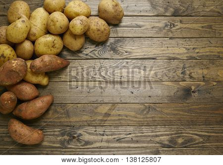 Potatoes and yams arranged on a reclaimed wooden table top background forming a page border
