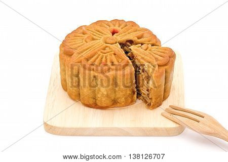 Mooncake with fork on wooden plate for the chinese Mid Autumn festival, on white background