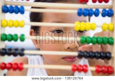 Close-up of girl playing with abacus in classroom