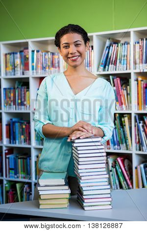 Portrait of young woman standing against bookshelf in library