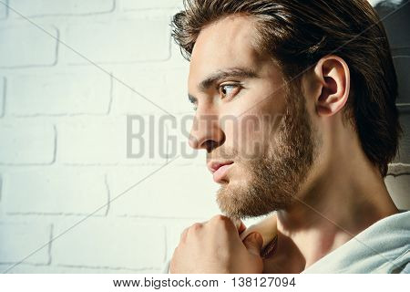 Beauty portrait of a handsome pensive young man standing by a white brick wall. Men's beauty, fashion.
