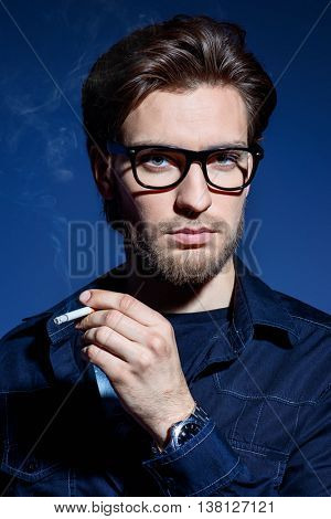 Attractive young man thoughtfully and calmly smoking a cigarette. Men's beauty, fashion. Optics style.