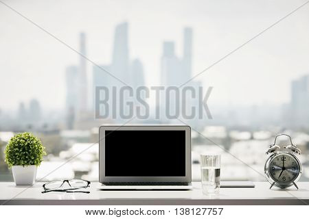 Closeup of blank laptop on windowsill with a glass of water alarm clock glasses decorative plant and other items on blurry city background. Mock up