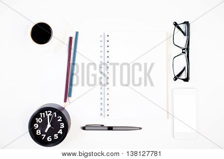 Top view of bright office table with blank spiral notepad other stationery items coffee cup glasses clock and blank white cellular phone. Mock up
