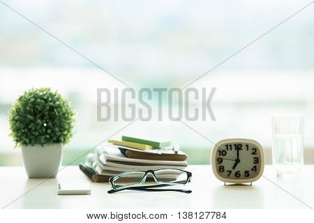 Closeup of bright desktop with glasses pile of textbooks decorative plant water glass and clock on blurry background. Education concept