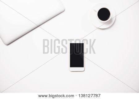 Top view of white desktop with closed laptop coffee cup and blank cell phone. Mock up