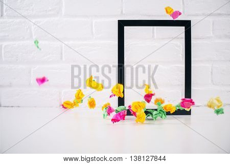 Decorative picture frame and colorful crumpled paper pieces on white brick background. Mock up