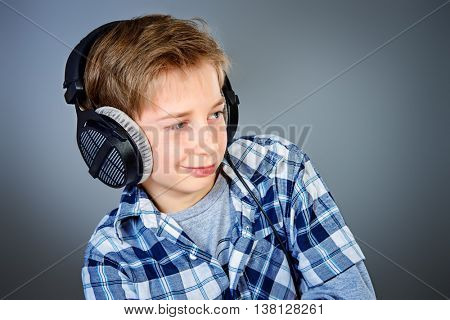 Cheerful teen boy listening to music in headphones. Studio shot.