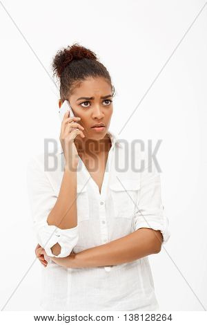Portrait of upset young beautiful african girl speaking on phone over white background.