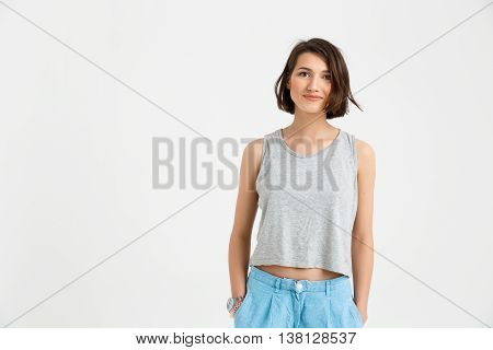 A portrait of young smiling beautiful girl, in gray shirt and blue jeans, looking at camera, keeping hands in pockets, isolated on white background