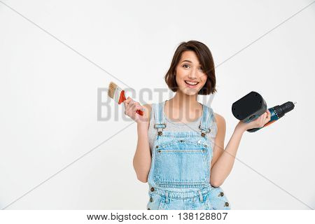 A portrait of young smiling  beautiful girl, in gray shirt and denim overall, holding painting brush and drill, looking at camera, isolated on white background