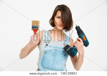 A portrait of young  beautiful girl, in gray shirt and denim overall, holding painting brush and drill, looking at camera, isolated on white background
