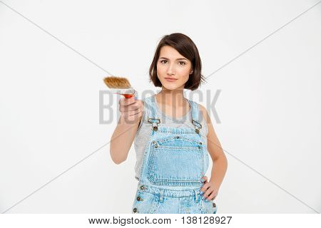 A portrait of young  beautiful girl, in gray shirt and denim overall, pointing forward with painting brush, looking at camera, isolated on white background