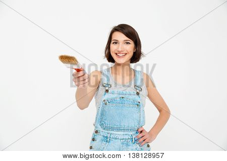 A portrait of young  beautiful smiling girl, in gray shirt and denim overall, pointing forward with painting brush, looking at camera, isolated on white background