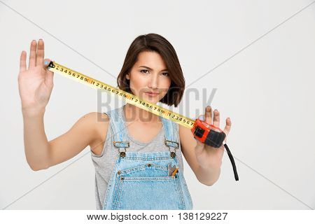 A portrait of young beautiful girl, in gray shirt and denim overall, showing tape measure, looking at camera, isolated on white background