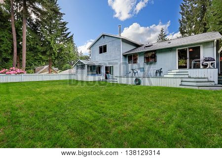 Fenced Back Yard Garden With Green Grass And Small Wooden Deck
