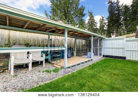 Covered Patio Area With Outside Chairs In The Backyard Garden.