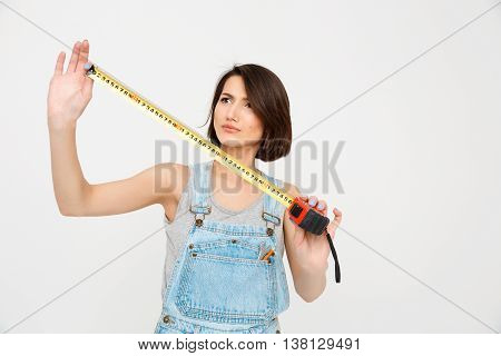 A portrait of young beautiful girl, in gray shirt and denim overall, looking on the tape measure, isolated on white background