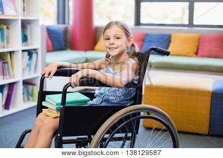 Portrait of disabled school girl with books in library