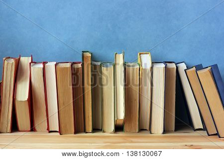 Books in colorful covers on a shelf against a blue wall. Back to school.