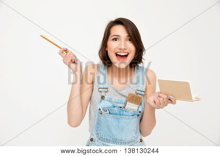 A portrait of young laughing beautiful girl, in gray shirt and denim overall, holding notebook, looking at camera, isolated on white background