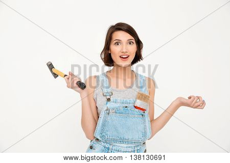 A portrait of young surprised beautiful girl, in gray shirt and denim overall, holding hammer, looking at camera, isolated on white background