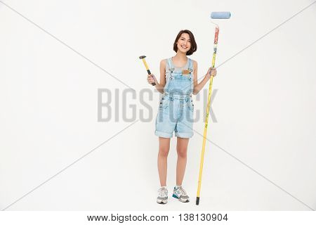 Full length portrait pretty girl, in gray shirt and denim overall, holding hammer and painting roller, isolated on white background