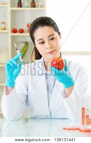 Biotechnology Engineer Examining Genetic Modification Apple