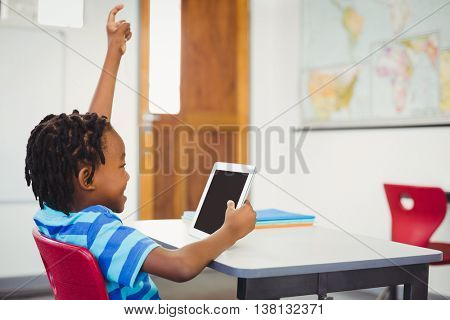Happy schoolboy sitting on chair and using digital tablet in classroom at school