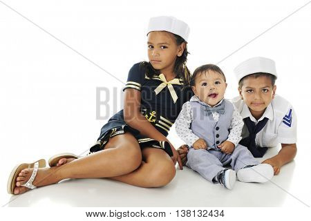 Three young siblings happily sitting in their sailor outfits.  On a white background.